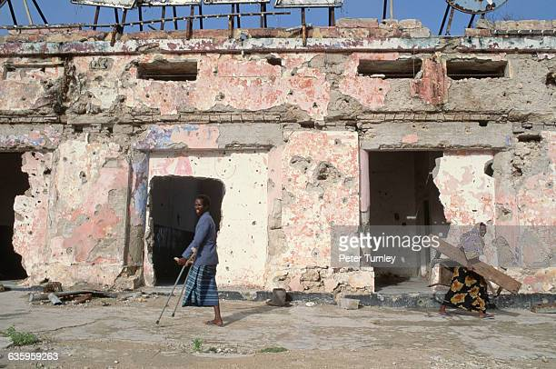 A woman with only one leg uses crutches to walk past a decrepit building which shows evidence of bombing and shelling In the 1980s civil war erupted...