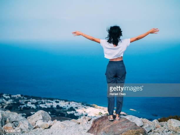 Woman with open arms on the top of the cliff