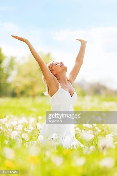 Mujer con las manos relaja en un día de sol.