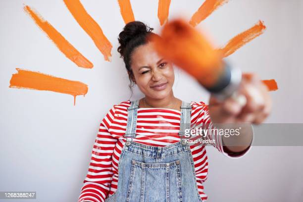 woman with orange brush strokes on wall - focus on background stock pictures, royalty-free photos & images
