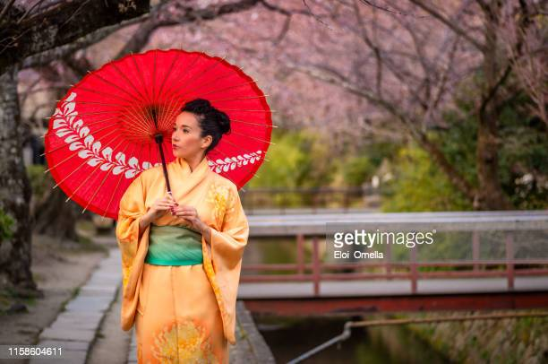 woman with orange kimono and red umbrella at philosopher's walk in kyoto, japan - kimono stock pictures, royalty-free photos & images