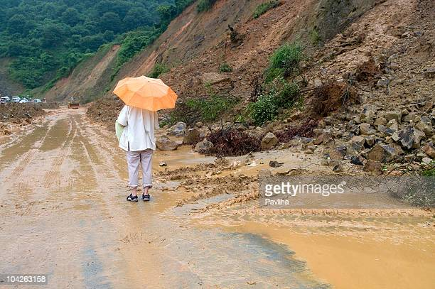woman with orange umbrella muddy road china - landslide stock pictures, royalty-free photos & images