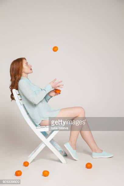 Woman with oranges on chair