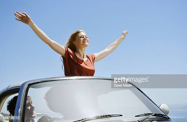 Woman with out stretched arms in open toped car