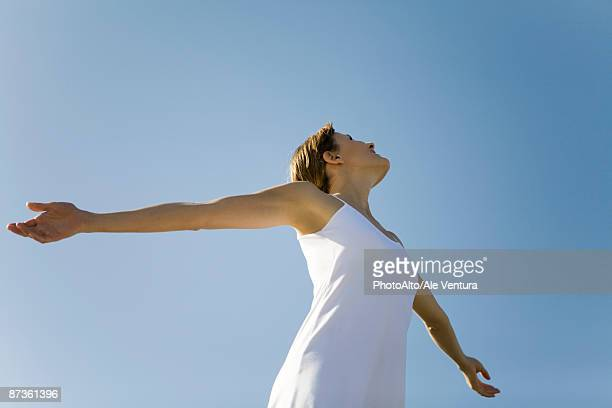 Woman with outstretched arms, looking up, low angle view