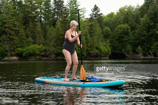 """50+ woman with paddleboard on a lake. - """"martine doucet"""" or martinedoucet stock pictures, royalty-free photos & images"""