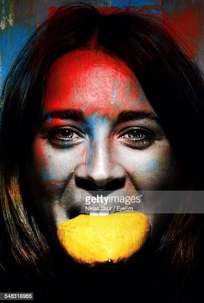 Woman With Painted Face Eating Lemon