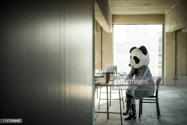 woman with panda mask sitting in office, thinking - パンダ ストックフォトと画像