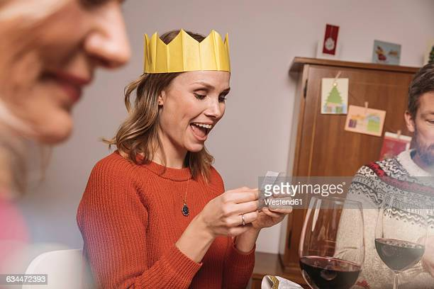 woman with paper crown reading a poem from her christmas cracker - crown stock photos and pictures