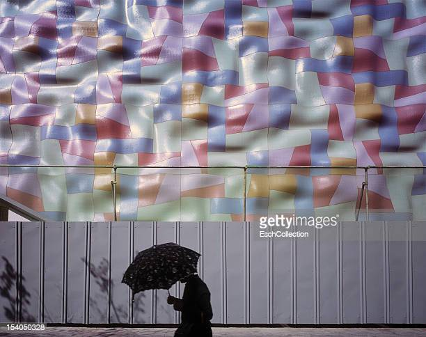 Woman with parasol passing colorful building site