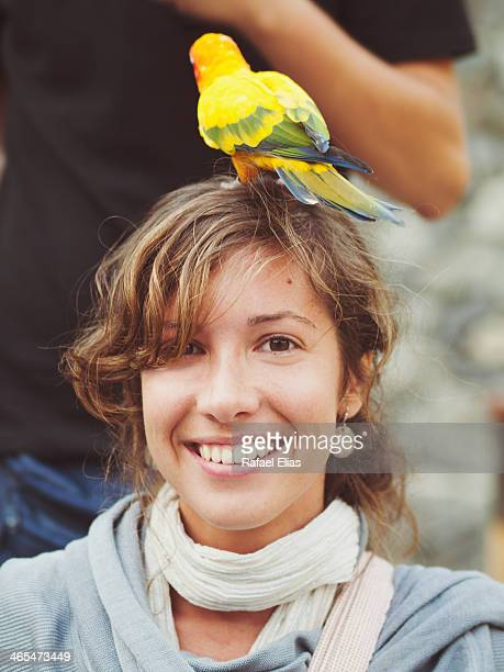 woman with parrot on head - braune augen stock-fotos und bilder