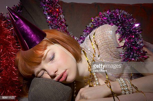 woman with party hat asleep on sofa
