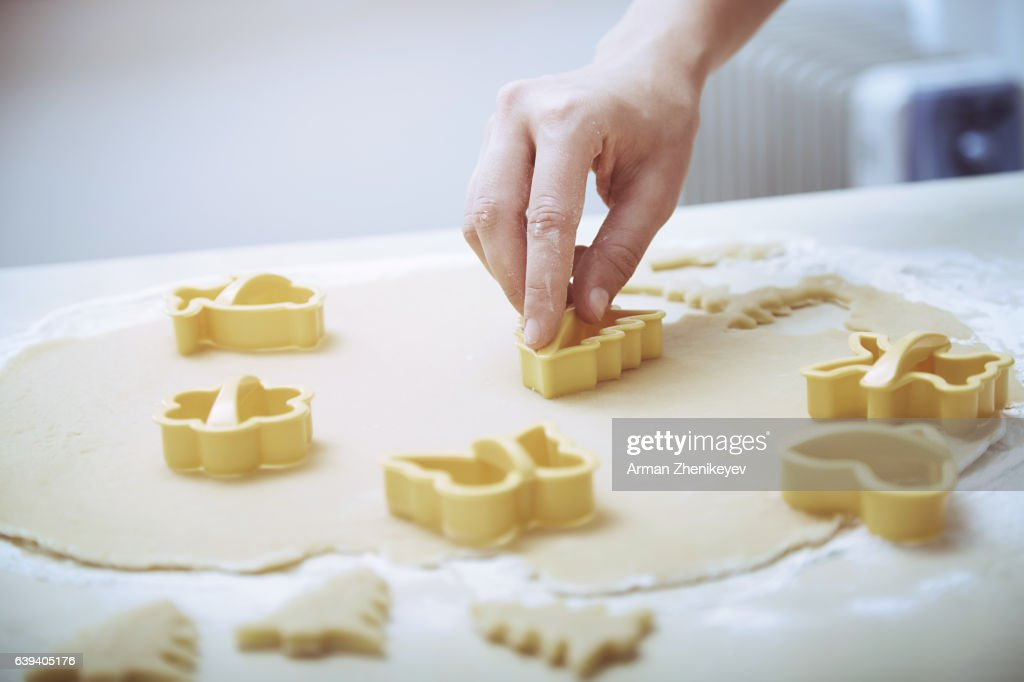 Woman with pastry cutter making holiday cookies : Stock Photo
