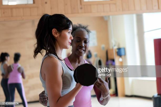 woman with personal trainer lifting weights in gym - fitness instructor stock pictures, royalty-free photos & images