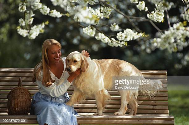 Woman with pet dog, sitting on bench