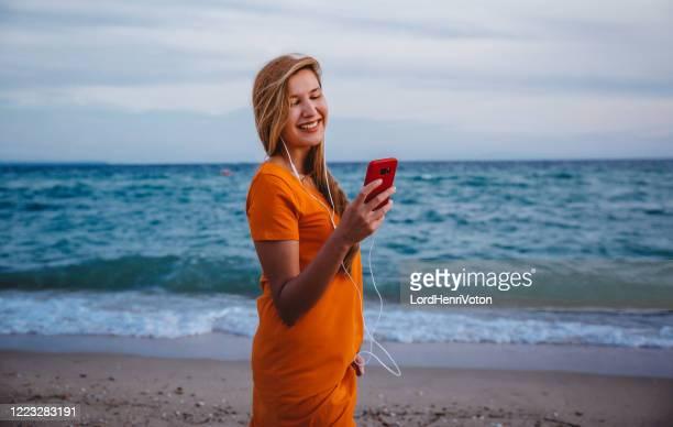donna con telefono e auricolari in spiaggia - henri coste foto e immagini stock