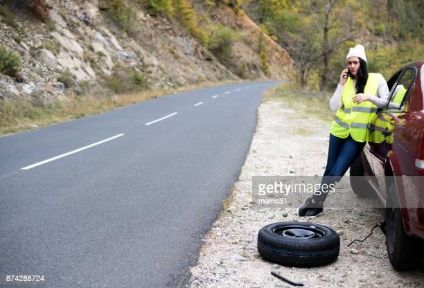 Mujer con el teléfono está llamando en el servicio de coche