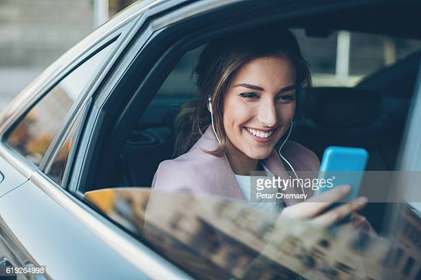 woman with phone on the back seat of a car - passagier stock-fotos und bilder