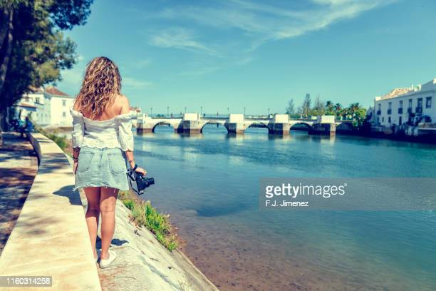 woman with photo camera in front of the roman bridge of tavira - free up skirt pics stock photos and pictures