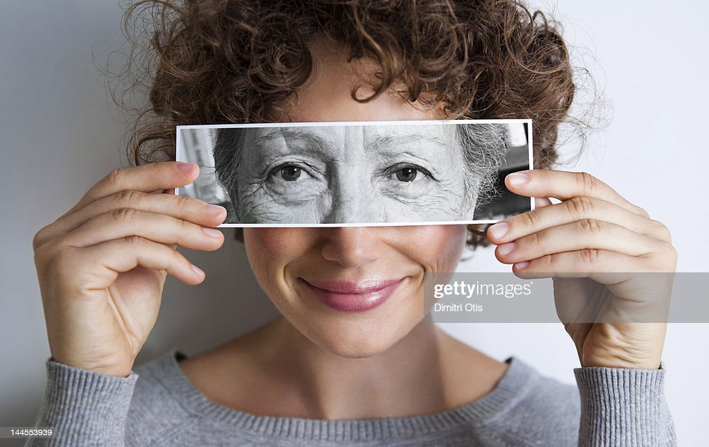 Woman with photo of elderly woman's eyes on hers' : Stock Photo