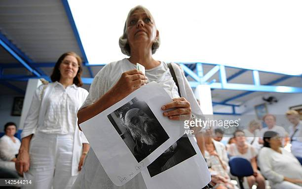 A woman with photos of relatives waits to enter in the Joao de Deus office at the 'Casa de Dom Inacio de Loyola' in Abadiania 120km southwest of...