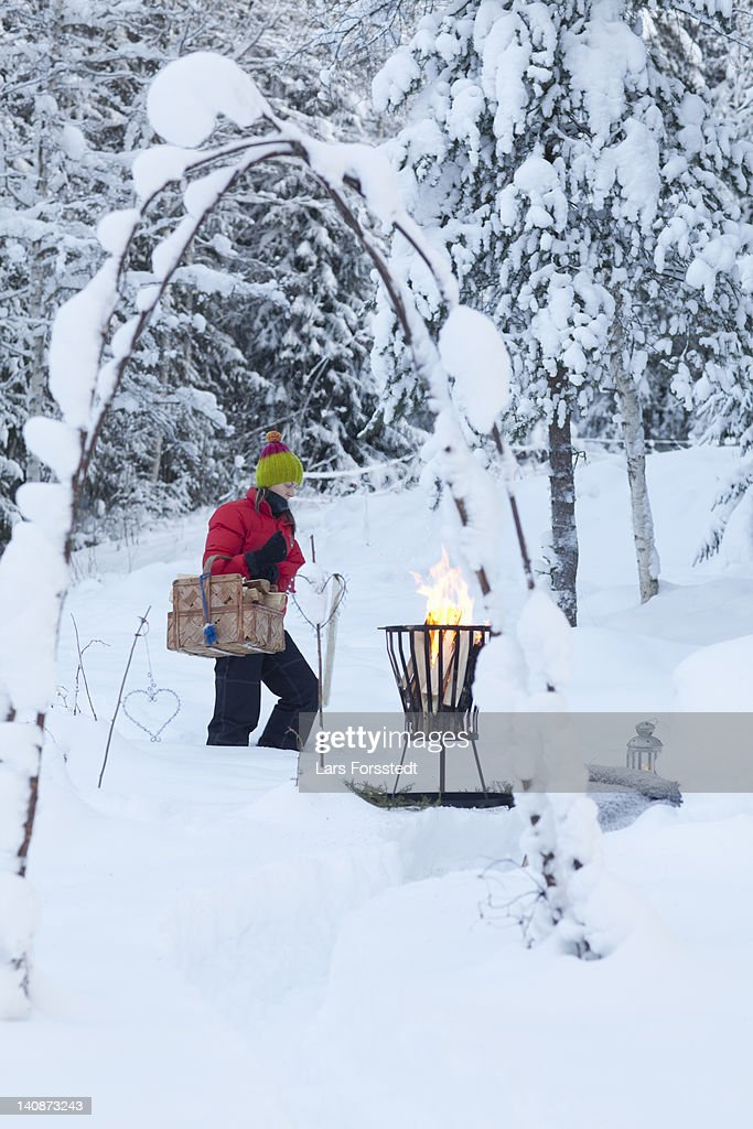 Woman with picnic basket in snowy field : Stock Photo