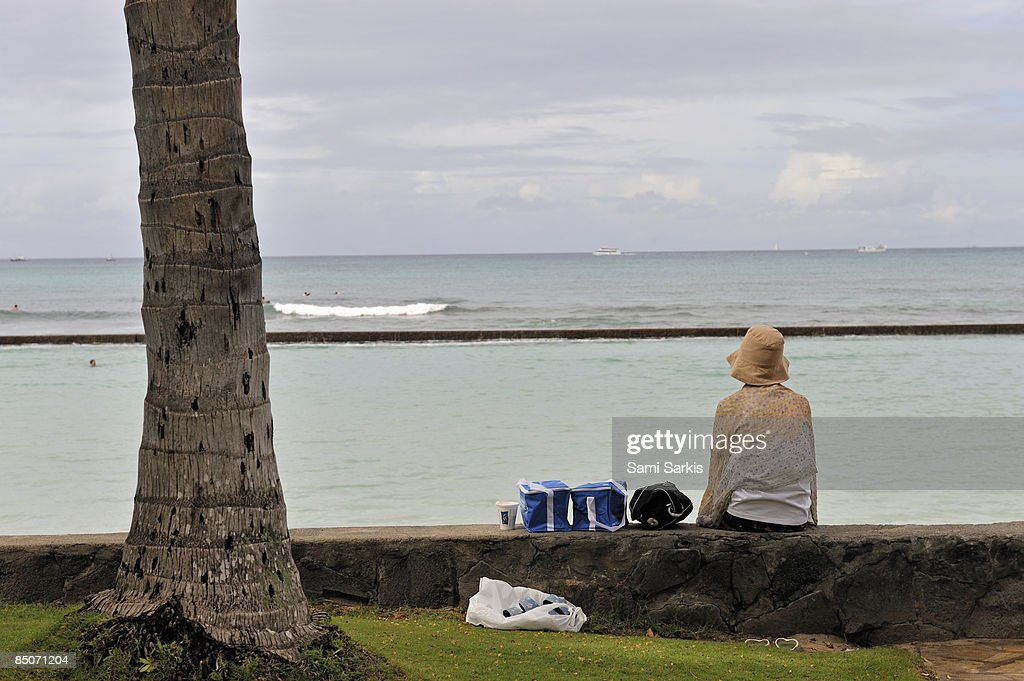 Woman with picnic set looking at ocean : Stock Photo