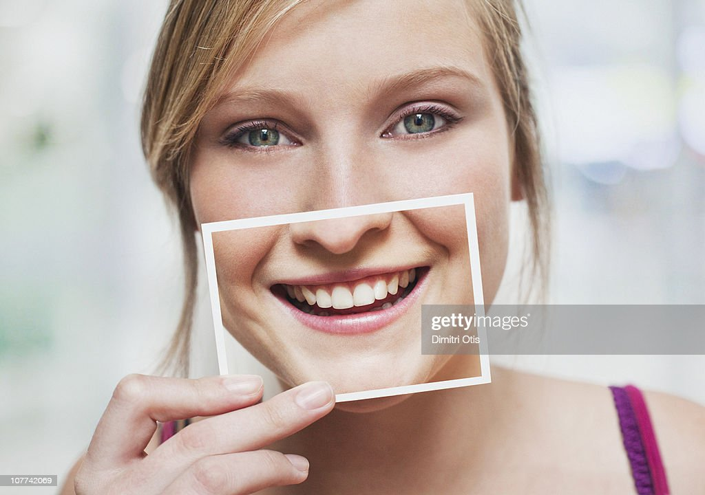 Woman with picture of her smile over her mouth : Stock Photo