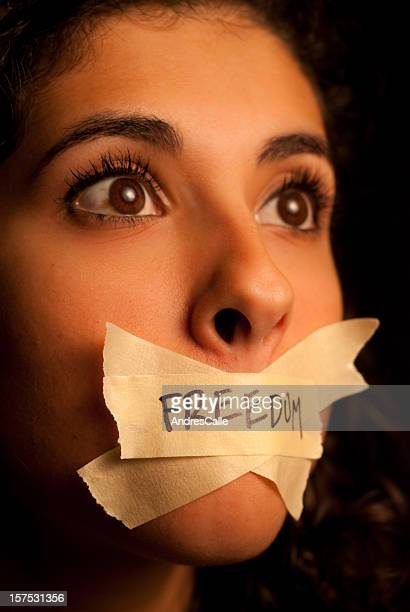 Woman with pieces of tape with the word freedom on her mouth
