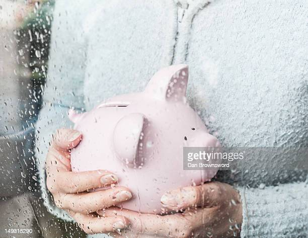 Woman with piggy bank at rainy window