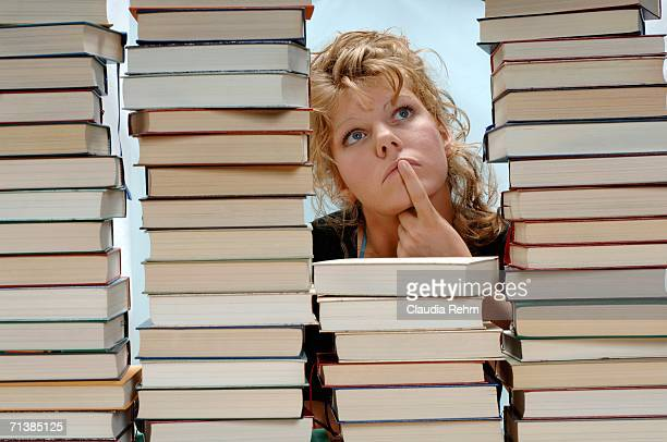 Woman with pile of books, looking up