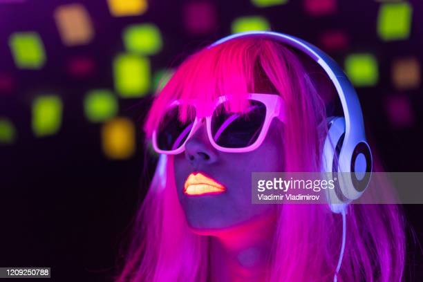 woman with pink colored hair and sunglasses listening music - fluorescent light stock pictures, royalty-free photos & images