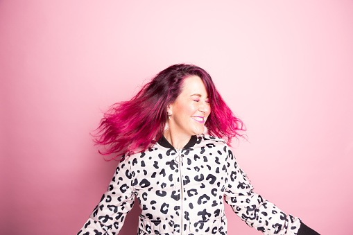 A woman with pink hair dances in front of a pink background - gettyimageskorea