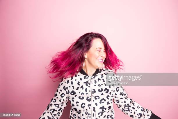 a woman with pink hair dances in front of a pink background - fashionable stock pictures, royalty-free photos & images