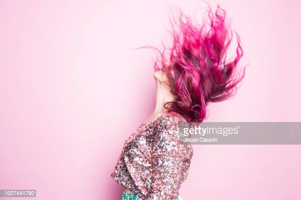 a woman with pink hair throws her head back - shot against a pink background - pink hair stock pictures, royalty-free photos & images