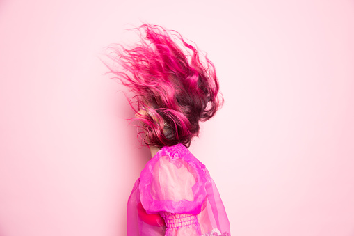 A woman with pink hair throws her head back so that her hair covers her face in front of a pink background - gettyimageskorea