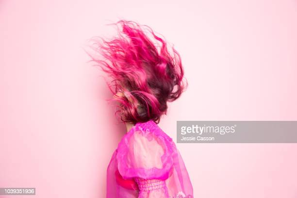 a woman with pink hair throws her head back so that her hair covers her face in front of a pink background - funky stock pictures, royalty-free photos & images