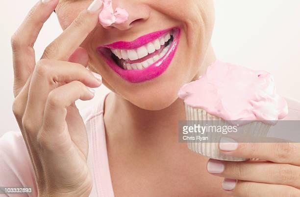 Frau mit rosa Lippenstift und Zuckerguss auf Nase Essen cupcake