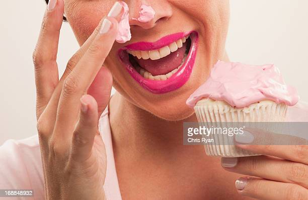 Woman with pink lipstick and frosting on nose eating cupcake