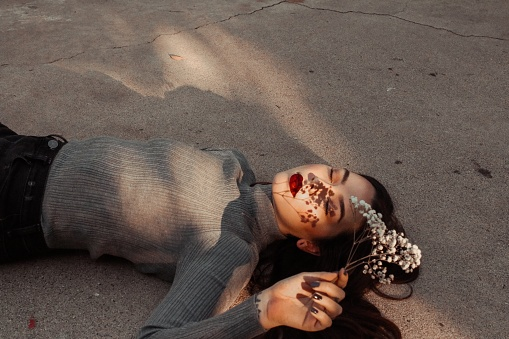Woman With Plant Lying Down On Sand - gettyimageskorea