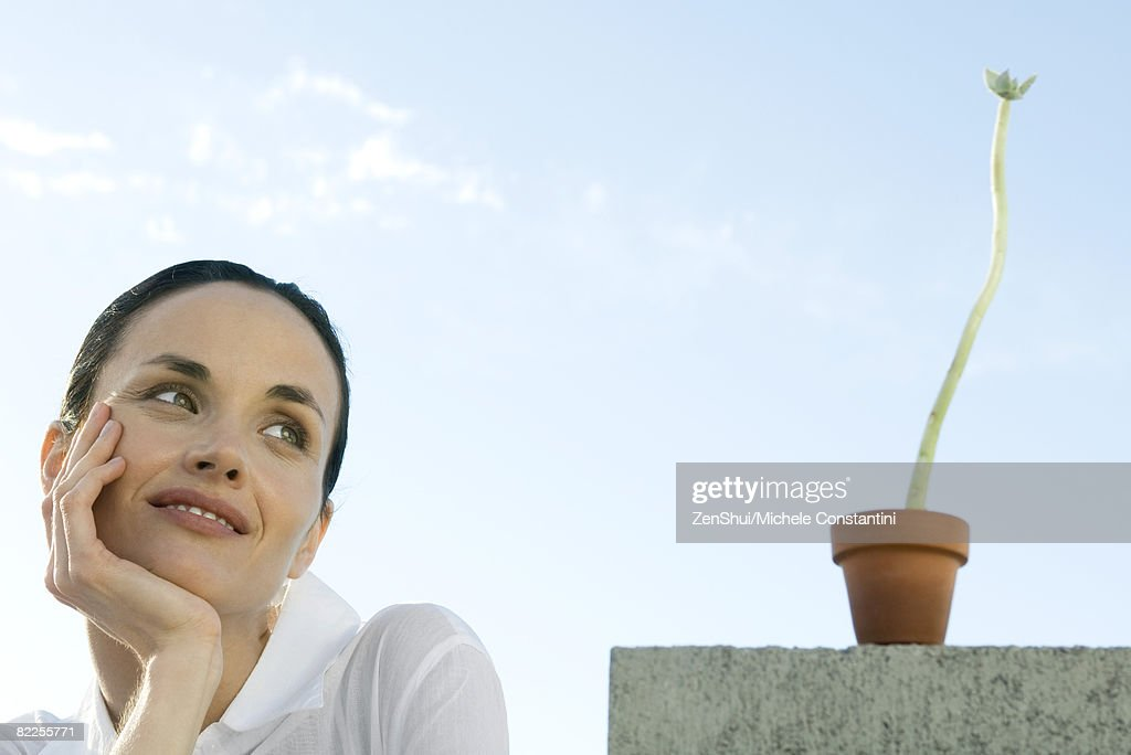 Woman with plant, smiling : Stock Photo