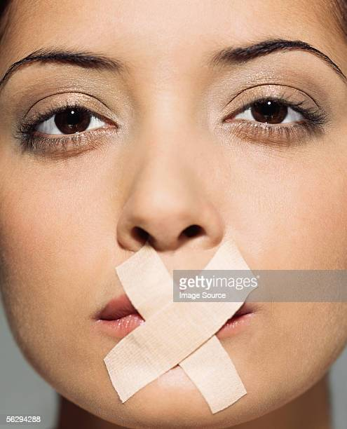 woman with plasters over her mouth - gagged woman stock pictures, royalty-free photos & images