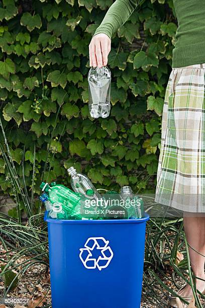 Woman with plastic bottle and recycling bin