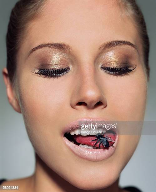 Woman with plastic fly in her mouth