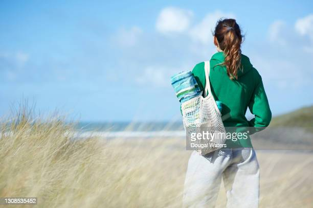 woman with plastic free reusable bag looking out to sea from beach. - dougal waters stock pictures, royalty-free photos & images