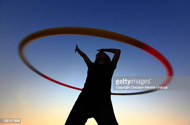 Woman with plastic hoop at sunset