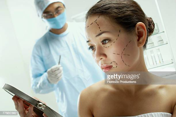 Woman with plastic surgery lines drawn on face