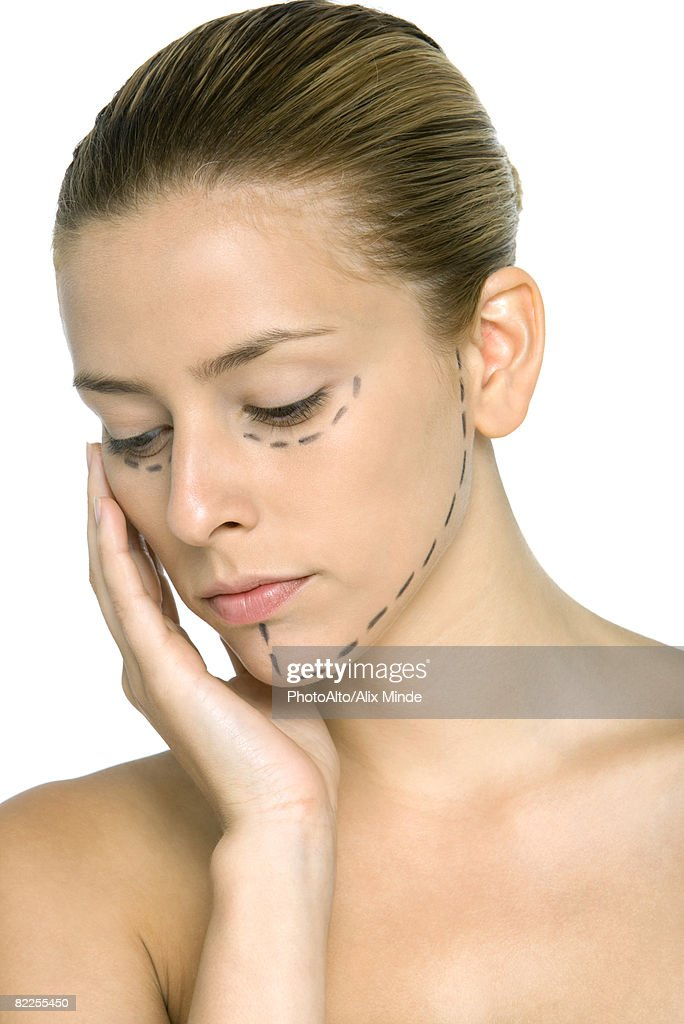 Woman with plastic surgery markings on face, hand under chin, looking down : Stock Photo