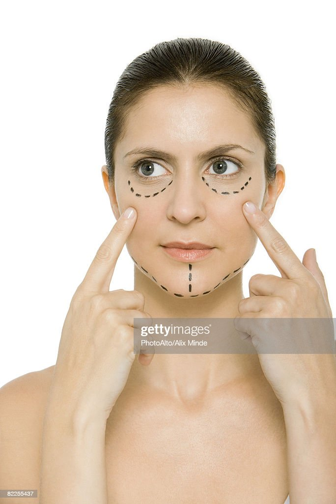 Woman with plastic surgery markings on face, touching cheeks, looking away : Stock Photo