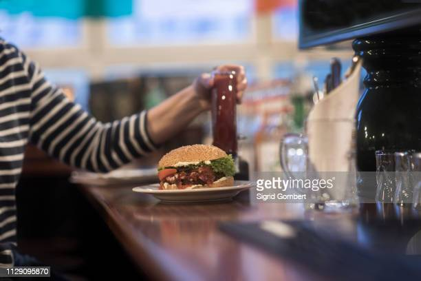 woman with plate of burger on pub counter top - sigrid gombert stock pictures, royalty-free photos & images